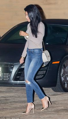 Casual chic: The mother-of-three tucked a slim grey top into her ripped skinny jeans