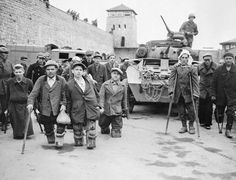 Russian and Polish prisoners stand in front of a US armoured vehicle belonging to the US 11th Armoured Divison. This image was taken at Mauthausen.