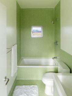 Small bathroom with green mosaic tiles and short bath tub.