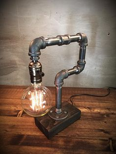 Industrial Lamp-Rustic Edison Table Lamp-Steampunk Reading Desk Light-Pipe lamp-Vintage lamps-Globe Edison Bulb INCLUDED-Weathered Wood Base  ADD ON: We offer a full range dimming socket to set just the right mood! The dimmer comes in silver and brass, this dimmer is available in our shop as an add on purchase!.  ***Choose Socket Color & Edison Bulb Style***  ITEM DETAILS -Measures 6W, 14H -Cord length 8F -Choose between silver or brass sockets (brass socket example can be viewed in…