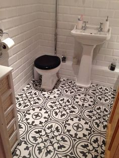 A Victorian era monochrome floor gives this white bathroom a rich, patterned footprint