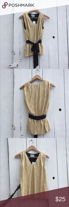 Sleeveless gold top with black ribbon belt This gold top would be great for a night out. It's never been worn and still has the tags! The black ribbon belt is sewn on at back and adjustable at the front. skies are blue Tops Blouses