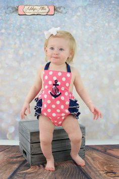 This ruffled sunsuit is perfect for summer! Coral pink and white polka dot fabric with navy ruffles. Includes a navy anchor monogram. Please