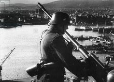 A German soldier stationed by an anti-aircraft machine gun at a defense in Oslo, 1940 (b/w photo)