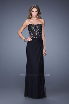 Striking net jersey dress with lace corset bodice. The skirt is softly gathered at the hip where it splits into a sheer slit that is accented with lace. The back is sheer embellished with lace.