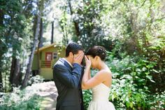 bride and groom Jordan and David show their excitement as they cover their eyes for their first look while standing on the pathway to their bridal cottage in the woods at their pema osel ling retreat center wedding in the santa cruz redwood mountains in corralitos, ca