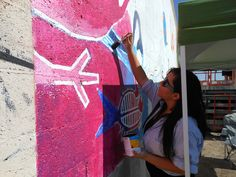 Jasmine fills in the shapes for phase 2 of the outdoor mural.