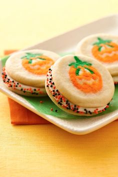 Frosting and sprinkles sandwiched between pumpkin shapes sugar cookies!