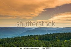 Beautiful landscape with dark green mixed forests and hills and a cloudy sky in the twilight hour/Hills and forests at sundown/Colorful landscape with trees - stock photo