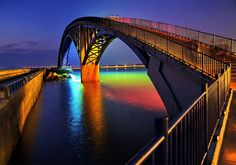 Rainbow Bridge in Penghu Taiwan illuminated Xiying is an elevated pedestrian walkway located in Magong, Penghu County in Taiwan. The bridge is lined with a thin neon band that reflects a rainbow onto the water's surface below at night Pedestrian Bridge, Light Installation, Rainbow Bridge, Beautiful Places, Beautiful Pictures, Around The Worlds, Rainbows, Rainbow Magic, Neon Rainbow