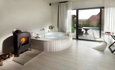http://www.justsoakit.com/wp-content/uploads/2015/01/winsome-bathroom-scandinavian-style-design-with-round-bathtub-corner-as-well-wooden-floor-including-elegant-pellet-stove-as-well-white-curtain-wide-glass-window-970x595.jpg