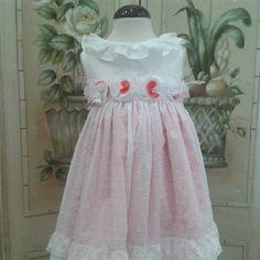 Vestido blanco de plumeti con escote trasero de pico y forro coral, combinado con fajin de flores en coral  y blanco.  Cubete´s Kids - www.cubeteskids.es