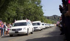 Hearses carrying the 19 fallen firefighters drive through Whiskey Row in downtown Prescott.