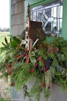 Bird house in window box with a mixture of evergreens and swag of tartan ribbon for Christmas #PottingShed | homeiswheretheboatis.net