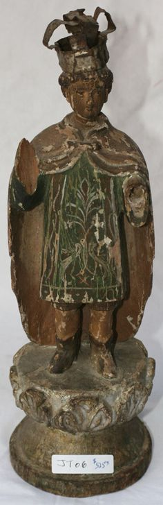 Antique wooden Philippine Santos statues are carved and painted religious statues of Christian saints, angles, or other religious figures. This Santos is of a crowned young boy, possibly a depiction of Jesus, wearing a regal green garment, long cape with painted emblems and brown boots. He is missing both of his removable hands-a fate not uncommon for older Santos. www.silkroadcollection.com/jt306x-filipino-antique-saint-statue.html