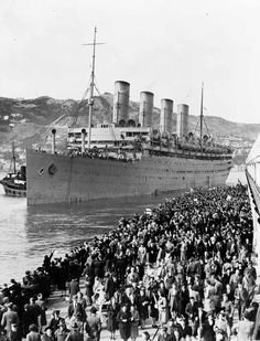 Troopship Aquitania - The Aquitania in Wellington Harbour. This luxurious and fast Cunard White Star liner served as a troopship throughout the Second World War. In 1940, when this picture was taken, it was carrying troops of the Second Echelon of 2NZEF. During the First World War the ship had carried 60,000 US troops and served as an armed liner, transport and hospital ship.