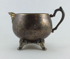 Oneida Silverplate De Maurier Creamer made in the USA  - 3 inches tall, 4 3/4 wide.  - Very tarnished  - lots of detail on handle, feet and spout.  - Oneida USA stamp on the bottom.