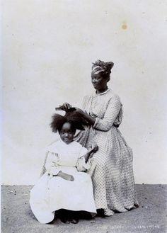 I really like this picture. Whenever we see pics of people doing black girls hair, there is always frowning and angry faces like its such a struggle. Here the little girl is smiling and content while her mother(??) is gently and patiently tending to her hair. It's nice.