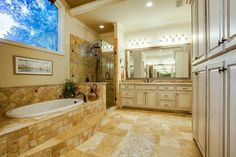 Luxurious master bathroom // Soaker tub under the window, large glass shower, dual vanities with granite countertops, oversized mirrors, tons of storage