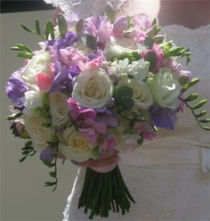 Hand tied of freesia, scabiosa and sweet peas with roses