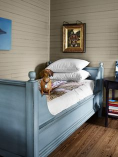Spare Sleeping Space    Dachshund Bosco poses in a corner of the master bedroom near his portrait, painted by Martha Bannon. Rachel Ashwell linens and a handmade quilt dress the Pottery Barn daybed.