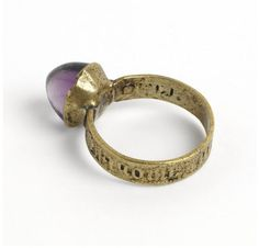 Latten (copper alloy) ring, the projecting bezel re-set with an amethyst, the shoulders stamped with roses. The hoop inscribed in black letters 'par / grant / amour', west Europe, ca.1400
