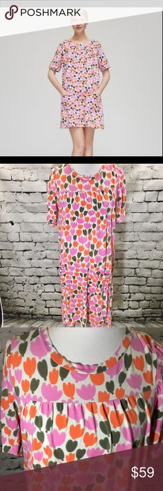 Marimekko Hiirenhattu Pink Floral T-Shirt Dress This is the Hiirenhattu dress by Marimekko. Allover pink, orange and and olive green buttercup / Tulip Floral print. Two front pockets. 95% cotton 5% elastane. In excellent condition. One small mark on flower at very bottom but not noticeable at all when wearing. Round neckline. Has a comfy, oversized fit so this could fit a variety of sizes. Features short sleeves. Marimekko Dresses