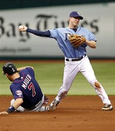 Tampa Bay Rays second baseman Elliot Johnson throws to first after forcing out Minnesota Twins' Joe Mauer during the fourth inning of a baseball game Sunday, April 22, 2012, in St. Petersburg, Fla. Josh Willingham was safe at first. The Rays won 6-2.