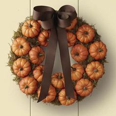 DIY wreath with moss/baby fake pumpkins/hot glue/spray adhesive/ribbon.