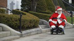 Mira estos singulares Papá Noel celebrando Navidad en el mundo Ken Keefner, vestido como Papá Noel, pasea en su silla de ruedas por Park Square en Pittsfield, Estados Unidos. (Foto: AP)