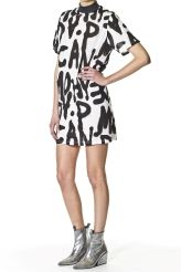 This is a short-sleeved T-shirt dress in white. It has a high collar in black and black and white spray paint print all over.