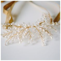 This is a very versatile design that can be worn as either a necklace or headdress when worn with the silk ribbons or, with the ribbons removed, it can be worn as a headpiece and pinned anywhere into your hair.  This is a more delicate design to the Mother of Pearl Gardenia and Tiny Rose version and is slightly smaller at approximately 8cm wide by 3.5cm deep and is cresent shaped.  Available in two colour options 1) gold wiring with clear crystals and ivory freshwater pearls or 2) silver…