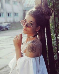 white offshouldress dress showing off a rose tattoo on a shoulder