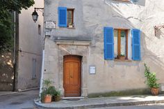 """Blue shutters at Cabasse's """"Place Jean Dotto"""". The street sign also says, """"Champion Cycliste, 13 Tours de France, 1951 - 1964 ~ Provence"""
