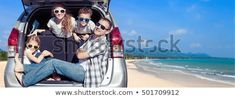 Happy father and children sitting in the car at the sunny day. People having fun outdoors. Concept of friendly family on vacation.