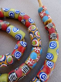 A beautiful strand of about 30 Mixed Glass Krobo beads from Ghana, on raffia 28 inches long. Each handmade bead measures from 12mm x 22mm. The hole is