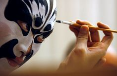 A man acting as the character Zhang Fei puts on makeup