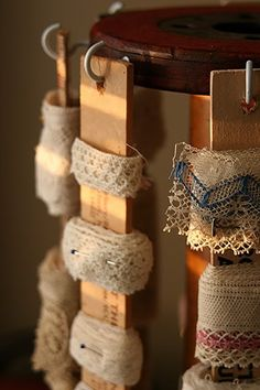 This would be cool in a sewing room.  Wrap lace around paint sticks and hang them from tea cup hools screwed into the sides of an old wooden spool.  I have several I use for candles.