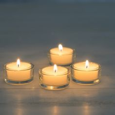 four Transparent Glass Tea Light holders with lit white candles