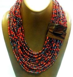 Balinese Beaded Necklace-Natural Wood Hook Buckle Closure-Multi Strand Glass Bead-Mix Red w/Black.  Features Stylish Wooden Buckle Enclosure Handmade from Bali Indonesia Multi-Stranded Beaded Jewelry You can twist it for a completely different look Size: Small to Medium Neck