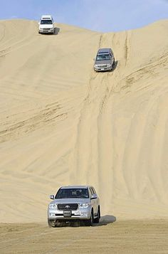 Three off-roaders driving in sand dunes, Emirate of Qatar, Persian Gulf, Middle…