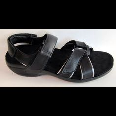 Aravon 'Kira' Black Leather Sandal These are in excellent, clean condition.   3 way Velcro adjustable straps to ensure a snug re provides a custom fit without laces Primalux Comfort Cushion--high density, open-cell foam that gently conforms to the foot and disperses pressure. Stability Cradle embedded in removable Velocor footbed supports the arch, cups the heel, and helps provide motion control. Comfort wedge sole for full ground contact MSRP $135.00 Aravon Shoes Sandals