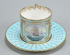 A Stefan Nowacki decorated (Derby) pale-blue-ground cabinet cup and saucer, painted with a seascape of a ship of the line under shortened sail, within an oval gilt and 'jewelled' border, with gilt monogram; and an additional saucer (see illustration)