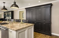 Classic black and white kitchen cabinets with tall pantry and expansive island. Shown in CliqStudios Austin inset door style.