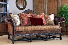 Old World style love seat with leather, exotic animal hide and eclectic floral print pillows