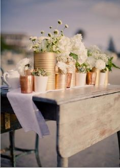 Spray paint tins to suit your colour theme, use them as a vase cluster centerpiece