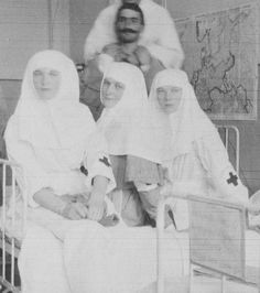 Empress Alexandra Feodorovna of Russia with her two eldest daughters,Grand Duchesses Olga and Tatiana Nikolaevna Romanova of Russia as Sisters of Mercys with a wounded soldier in