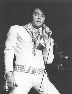 "J.A.T. Publishing © February 1970 Making his return to the International Hotel in Las Vegas, Elvis proved again that he still has the charisma and magnetism to pull 2, 000 people out of their chairs to give him several standing ovations. Elvis looked like a Greek God as he stood under the bright spotlights. He wore a "" mod "" outfit.... a white, long sleeved, French jump suit open at the chest. He wore a pearl beaded tie belt that hung loosely over his hip bugger pants. He had on a collar of…"