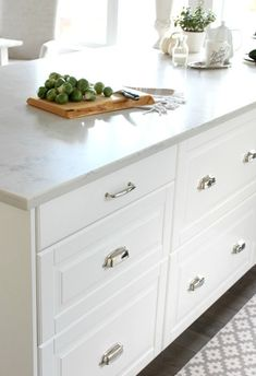 Bodbyn White Ikea Kitchen Island Drawers with Polished Nickel Cup Pulls - Marble Quartz Countertop - Satori Design for Living Ikea Bodbyn Kitchen, White Ikea Kitchen, Classic White Kitchen, Ikea Kitchen Cabinets, White Kitchen Island, Kitchen Flooring, Kitchen Countertops, New Kitchen, Kitchen Decor