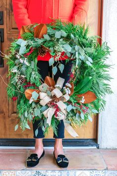 A burlap ribbon and spray of red berries brings a festive touch to this beautifully rustic flat cedar wreath. The perfect addition for your holiday decor! This wondrous wreath includes flat cedar, curly willow, seeded eucalyptus, and magnolia leaves.